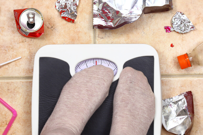 Feet on bathroom scale with junk food garbage around